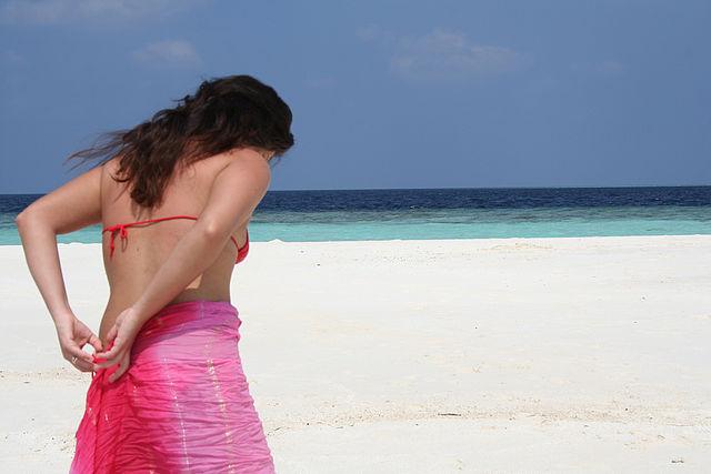 Une femme avec un paréo à la plage
