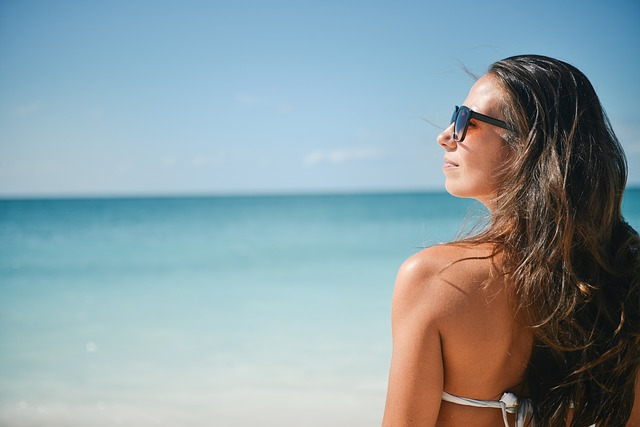 Une fille avec une paire de lunettes de soleil à la plage