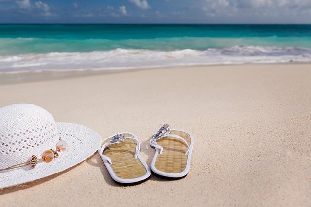 Une vue d'une paire de tongs à la plage avec un chapeau