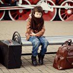 Un enfant en attente à l'arrivé à la gare avec ses bagages